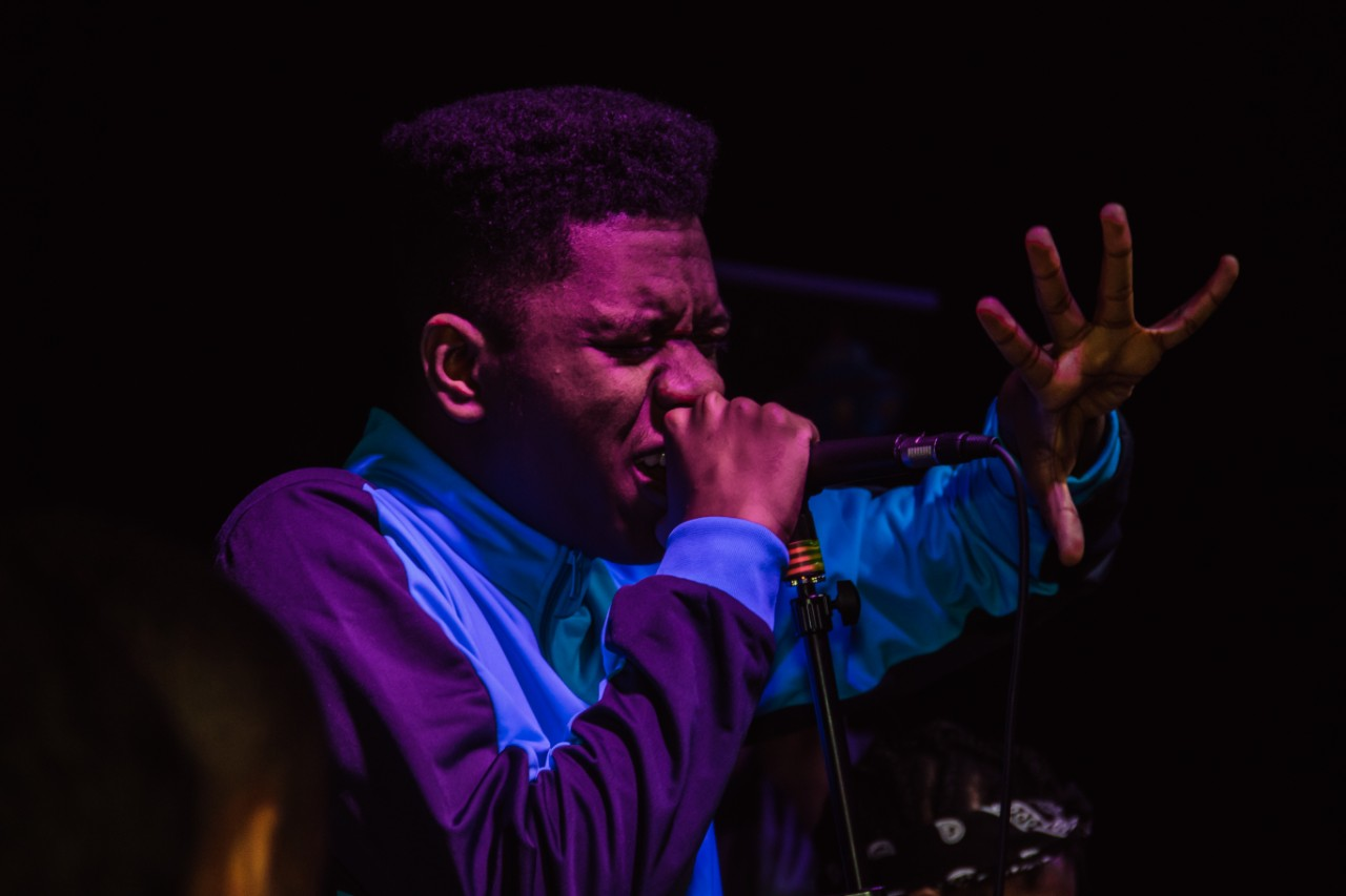 A young black man sings into a microphone. He raises his left hand emphatically
