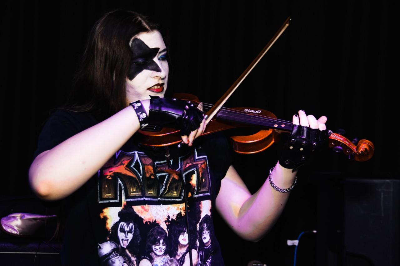 A young musician with a painted black star on their face, plays the violin